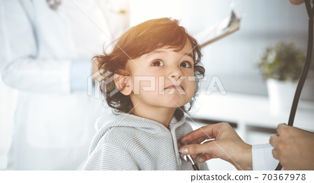 Woman-doctor examining a child patient by stethoscope in sunny clinik. Cute arab toddler at physician appointment 70367978