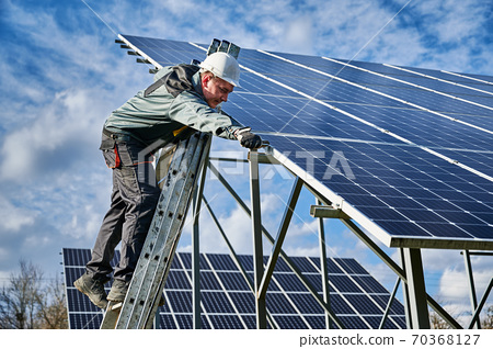 Male worker on solar plant installing solar batteries, standing on a ladder on a sunny day 70368127