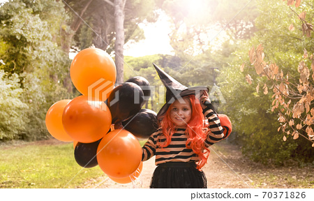 Little girl dressed as a witch with a candy bar in an autumn park. Happy Halloween holiday. The 70371826