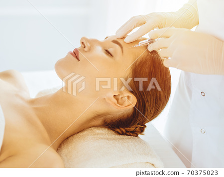 Beautiful woman receiving beauty injections with closed eyes in sunny medical center. Beautician doctor hands doing beauty procedure to female face with syringe 70375023