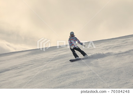 Female snowboarder in sun flare 70384248