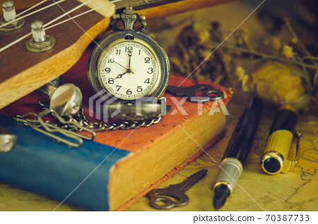 An antique pocket watch leaned against a ukulele and old book with vintage map and brass pen placed on wooden table. closeup and copy space for text. The concept of memories or things in the past. 70387733