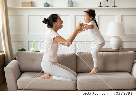 Overjoyed Asian woman with little girl jumping on couch 70388891