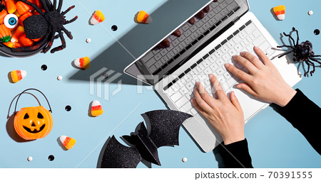 Halloween decorations with person using a laptop computer 70391555