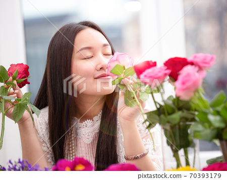 Woman Preparing to trim red and pink roses and beautiful flower arrangements in the home, flower arrangements with vase for gift-giving for Valentine's Day and Business in family on the on table 70393179
