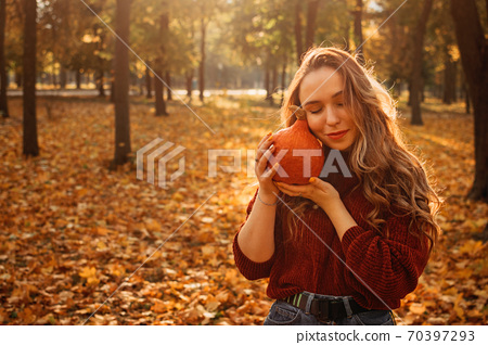 Young beautiful smiling woman with long curly hair holding orange halloween pumpkin on autumn park yellow trees background. Fall autumn halloween concept. 70397293