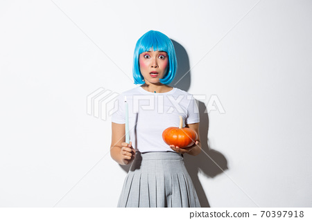 Concept of halloween. Image of scared asian girl in blue wig looking nervous and frightened, holding candle and pumpkin 70397918