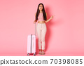 Travelling, holidays and vacation concept. Full-length of indecisive attractive asian girl making choice, pointing finger right while looking serious camera, standing with suitcase, pink wall 70398085