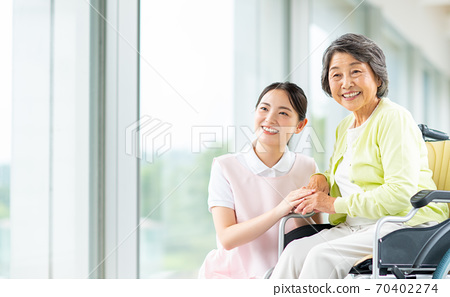 Elderly people in wheelchairs and care workers 70402274