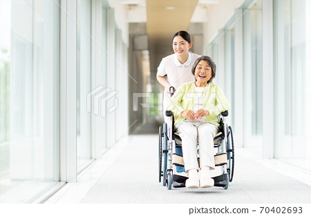 Elderly people in wheelchairs and care workers 70402693