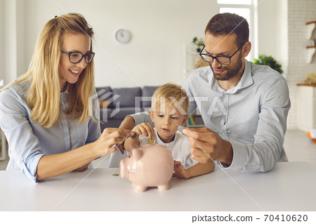 Curious little kid saving up money and learning about financial literacy from young parents 70410620