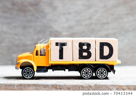 Truck hold letter block in word TBD (Abbreviation of to be defined, discussed, determined, decided, deleted or declared) on wood background 70413344