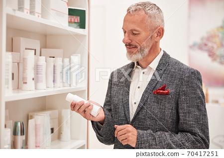 Focused senior citizen checking out a little white bottle 70417251