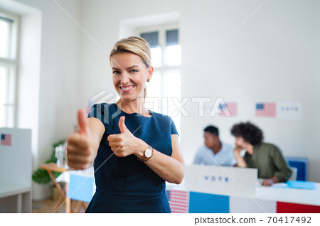 Portrait of happy woman voter with tumb up in polling place, usa elections concept. 70417492