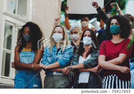 Group of people activists protesting on streets, women march, demonstration and coronavirus concept. 70417803