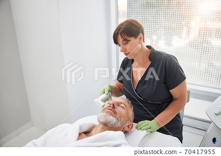 Careful cosmetician conducting skincare treatment for an aging man 70417955