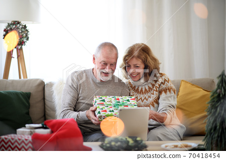 Front view of senior couple indoors at home at Christmas, having video call with family. 70418454