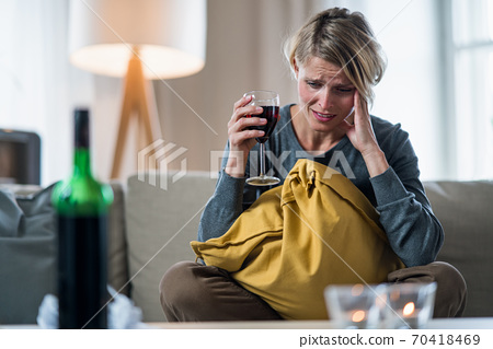 Depressed woman indoors at home, mental health and alcohol addiction concept. 70418469