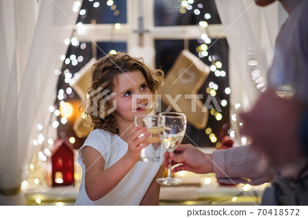 Small girl with family indoors celebrating Christmas together, clinking glasses. 70418572