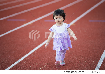 cute baby running at sport stadium 70424229