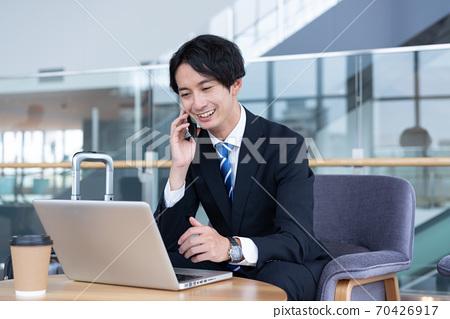一個微笑的年輕商人談話在他的智能手機在終端的大廳 70426917