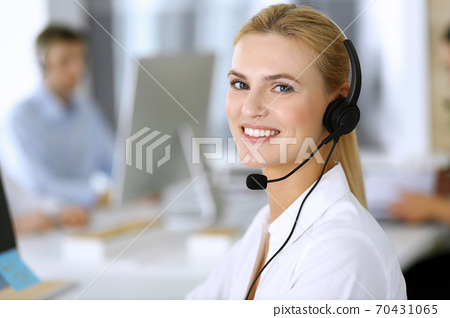 Blonde business woman using headset for communication and consulting people at customer service office. Call center. Group of operators at work at the background 70431065