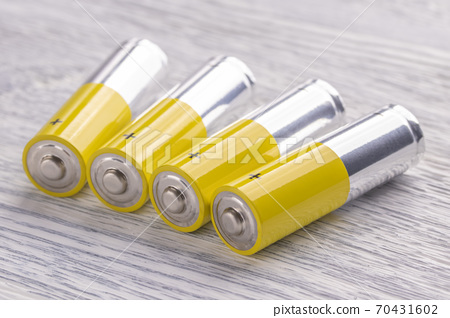 AA batteries on an old white wooden table. Reserve concept for future use 70431602