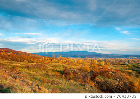 rural valley at sunset. beautiful autumn landscape in mountains. village in the distant valley. clouds on the blue evening sky 70433735