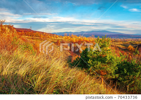 rural valley at sunset. beautiful autumn landscape in mountains. village in the distant valley. clouds on the blue evening sky 70433736
