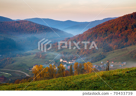 stunning rural landscape. foggy scenery at sunrise in autumn season. trees on mountain hills in colorful foliage. village in the valley 70433739