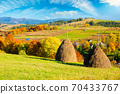 rural landscape in mountains. haystack on the hill. village in the valley. scenery in fall colors. beautiful sunny weather with fluffy clouds on the sky 70433767