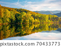 gilau lake of cluj country in evening light. beautiful landscape of romania in autumn. reflection on the calm water surface. trees in colorful foliage. sunny weather 70433773