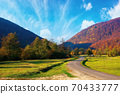 trees along the countryside valley. beautiful autumn scenery in mountains. forest on hills in fall colors. wonderful sunny weather. blue sky with clouds 70433777
