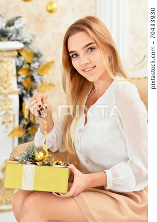 Close-up portrait of beautiful girl with gift in room 70433930