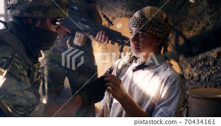 Teen terrorist near soldier at war 70434161