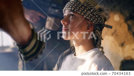 Teen terrorist near soldier at war 70434163