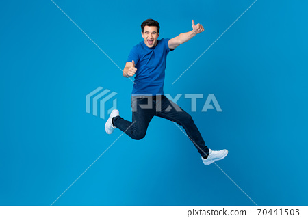 Smiling American man joyfully jumping and doing double thumbs up gesture 70441503