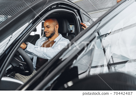 Young attractive woman salesperson in car showroom showing a car to her male client 70442487