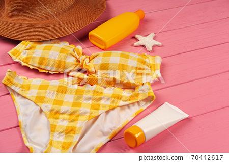 Yellow bikini on bright pink wooden background 70442617