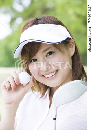 A woman with a golf ball 70443683