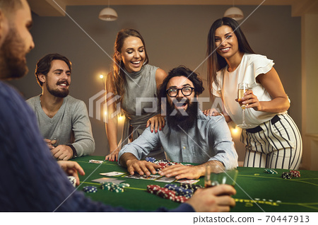 Excited poker winner sitting at casino table surrounded by happy friends drinking champagne 70447913