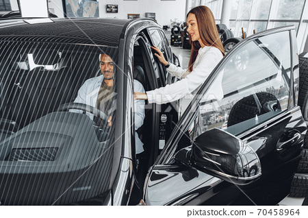 Young attractive woman salesperson in car showroom showing a car to her male client 70458964