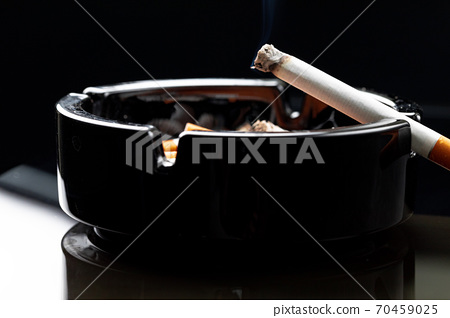 Burning cigarette in a black ash tray 70459025