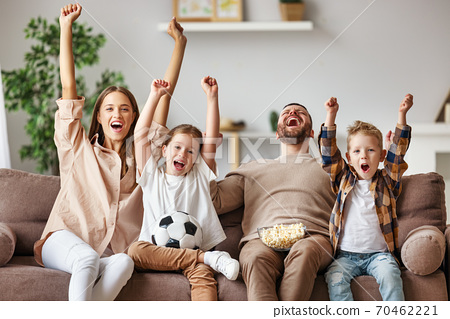 family of fans watching a football match and celebrating goal on TV at home. 70462221