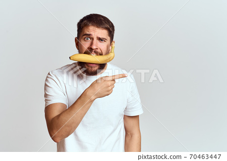 Cheerful man with a banana in his hands on a light background fun emotions Cropped view Copy Space 70463447