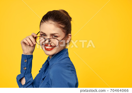 A woman in a blue shirt and glasses with bright makeup on her face is gesturing with her hands Copy Space 70464066