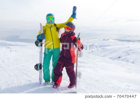 Two girls with snowboards together in snow having fun outside 70470447