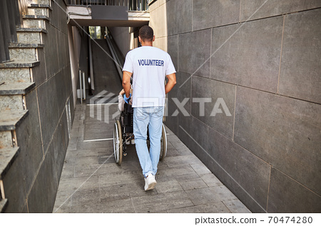 Volunteer pushing a wheelchair into an entrance for disabled 70474280