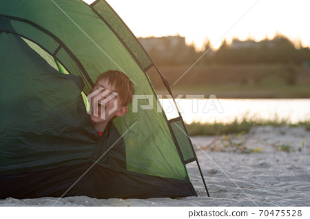 Child in tent yawns. Early morning at the campsite. Camping. 70475528
