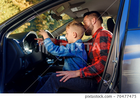 handsome father pointing on something while teaching teen son driving car 70477475